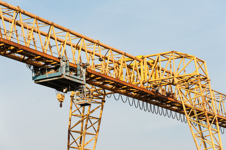 Yellow gantry crane with winch over bright blue sky