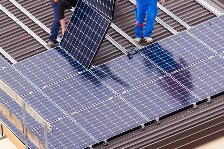 Photo pour Installation of solar panels on a roof. - image libre de droit