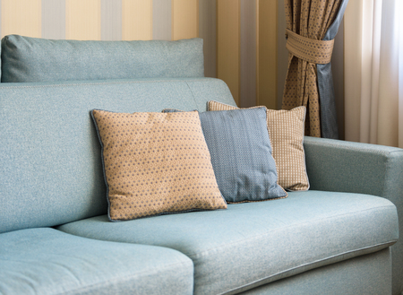 Foto de Couch or sofa with cushions in the home interior. Classic couch pillows close-up. Detail of the pastel interior of flat in daylight. - Imagen libre de derechos