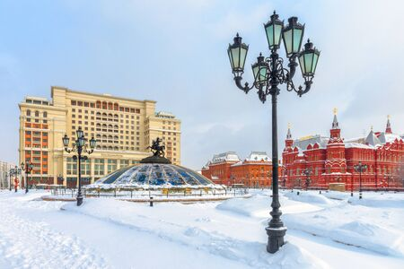 Foto de Moscow, Russia - Feb 5, 2018: Manezhnaya Square under snow in Moscow. Nice panoramic view of the snowy Moscow center in frosty winter. Dome with statue of St George and Four Seasons Hotel behind it. - Imagen libre de derechos
