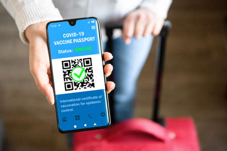 Photo pour COVID-19 vaccination passport in mobile phone for travel, tourist holds smartphone with health certificate app, digital coronavirus pass. Concept of corona virus, immunity passport and tourism. - image libre de droit