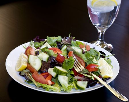 A Plate full of Organic Greens, Tomatoes, Cucumbers, Red Bell Peppers, and Fresh Lemon