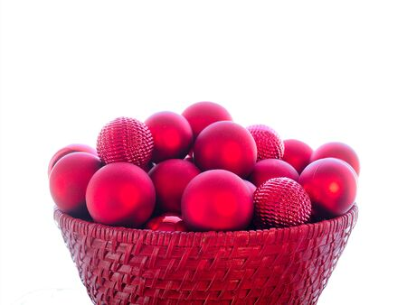 Close-up of red Christmas Bauble Balls in a red basket isolated on white background.