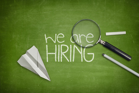We are hiring concept on green full frame blackboard with magnifying glass
