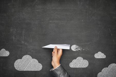 Photo pour Businessman hand holding paper plane on front of vintage full frame black blank blackboard no frame and couple clouds - image libre de droit