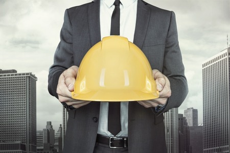 Businessman holding yellow helmet in hands with tie and shirt on cityscape background