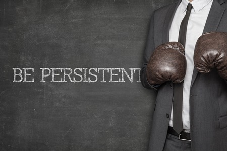Be focused on blackboard with businessman wearing boxing gloves