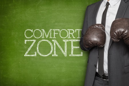 Comfort zone on blackboard with businessman wearing boxing gloves