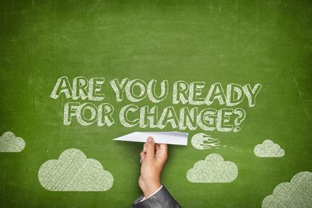 Foto de Are you ready for change concept on green blackboard with businessman hand holding paper plane - Imagen libre de derechos