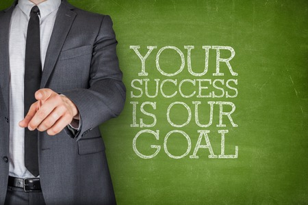 Your success is our goal on blackboard with businessman finger pointing