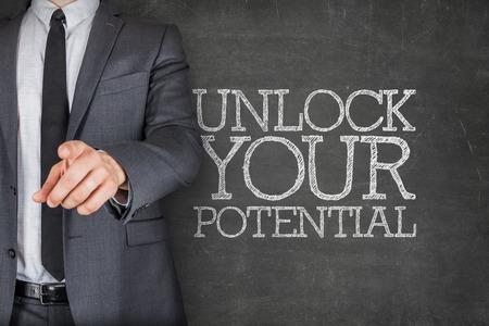 Photo pour Unlock your potential on blackboard with businessman finger pointing - image libre de droit