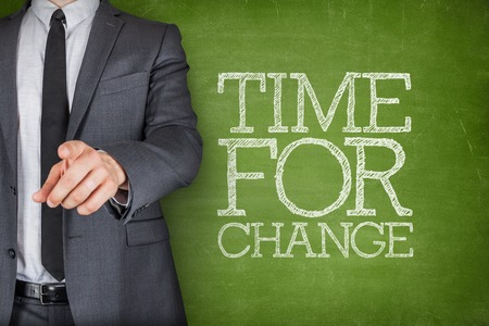 Time for change on blackboard with businessman finger pointing