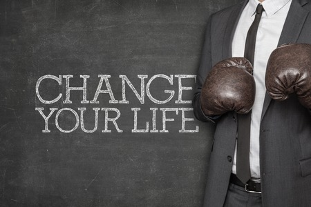 Change your life on blackboard with businessman wearing boxing gloves