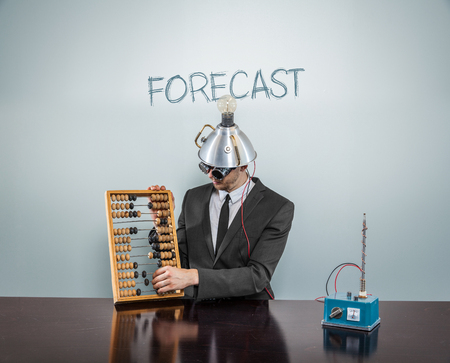 Forecast concept with businessman and abacus at office