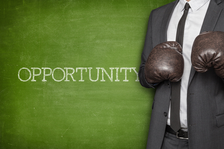 Opportunity on blackboard with businessman wearing boxing gloves