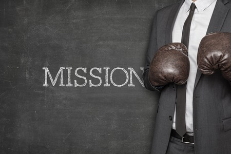 Mission on blackboard with businessman wearing boxing gloves