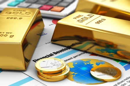 Business banking and financial success concept  gold ingots, coins and office calculator on colorful financial report documents with graphs, charts and stock market exchange data