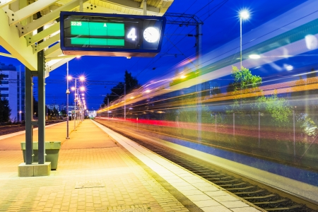 Railroad travel and transportation industry business concept  summer night view of high speed passenger train departing from railway station platform with motion blur effect