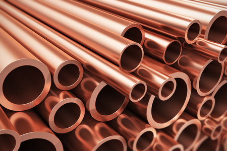 Creative abstract heavy nonferrous metallurgical industry and industrial manufacturing business production concept: heap of shiny metal copper pipes with selective focus effect