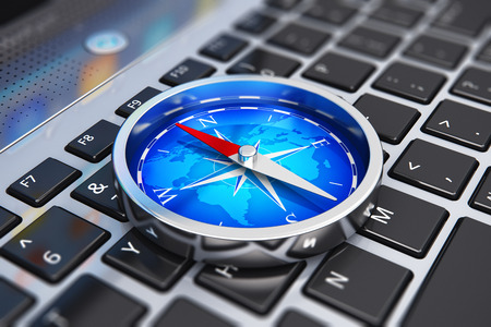 Creative abstract global web communication, wireless GPS navigation internet technology and success in business concept: macro view of shiny metal magnetic compass with red arrow and blue world map on laptop or notebook computer PC keyboard with selective