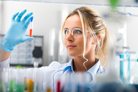 Young attractive female scientist in protective eyeglasses and gloves examining test tube with red liquid sample substance probe in the scientific chemical research laboratory