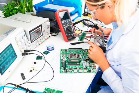 Photo pour Young attractive female digital electronic engineer checking green circuit board PCB in laboratory - image libre de droit