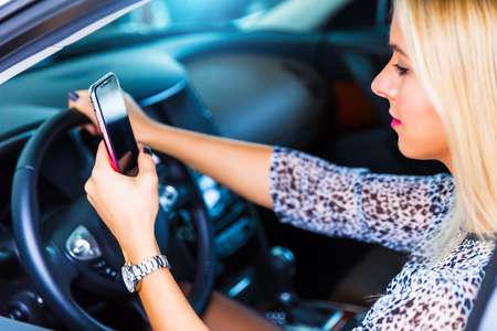 Photo pour Distracted young business woman driver using a smartphone and texting while driving a car on a highway - image libre de droit
