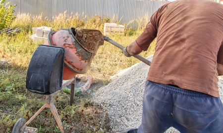 Foto de Worker kneads concrete at a construction site . - Imagen libre de derechos