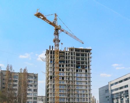 Photo pour Crane builds a tall house against the blue sky . - image libre de droit