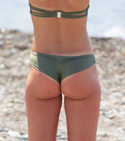 Photo pour Beautiful butt girl on the beach. Part of the human body. Summer vacation at sea - image libre de droit