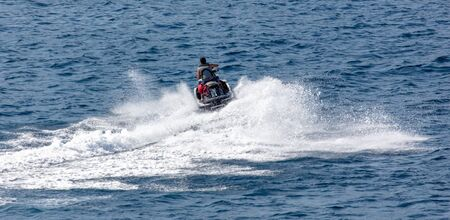 Photo for A motorcycle is racing in the blue water of the sea. - Royalty Free Image
