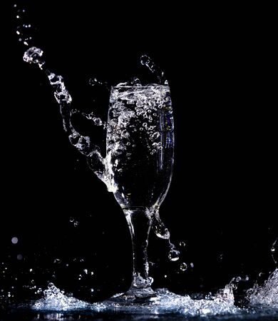 Photo pour Water with splashes in a glass on a black background. - image libre de droit