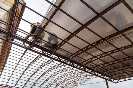 Photo pour A worker mounts a metal canopy in the courtyard of the house. - image libre de droit