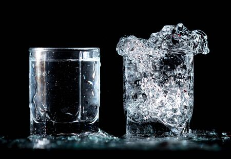 Photo pour Splashes and drops of blue water in two glasses are isolated on a black background. - image libre de droit