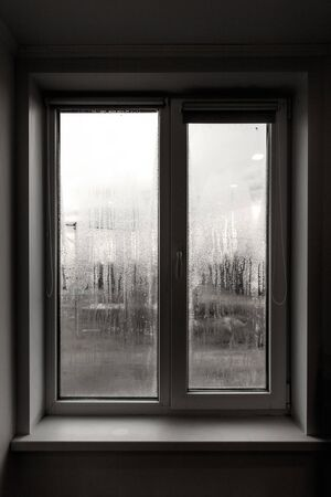 Photo pour A window with fogged glass in the room as a backdrop. - image libre de droit