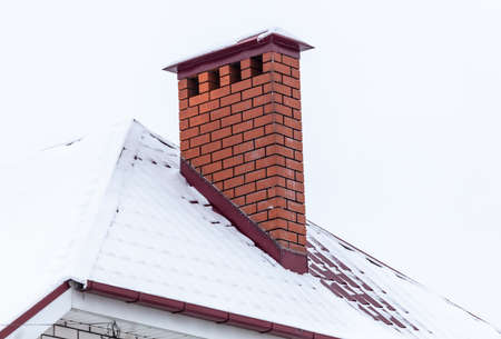 Photo pour Brick chimney in the snow on the roof of the house. Winter - image libre de droit