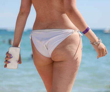 Photo pour Girl in a swimsuit on the beach near the sea. - image libre de droit
