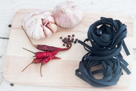 Squid ink black tinted twirl of a tagliatelle on table wood