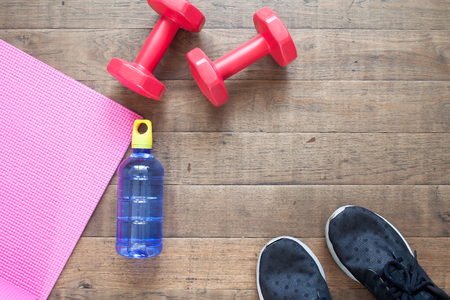 Creative flat lay of workout concept. Fitness equipment, water bottle and sport shoes on wooden floor