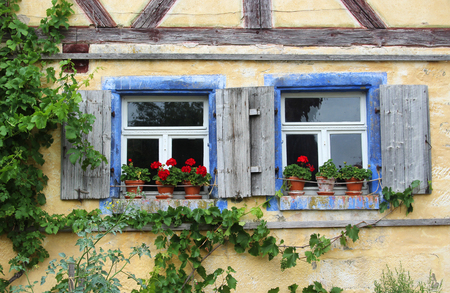 Photo pour Two old windows with shutters and red geraniums in a half-timbered house - image libre de droit