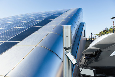 Photo for Electric car is charging near the station against the background of building with solar panels on roof - Royalty Free Image