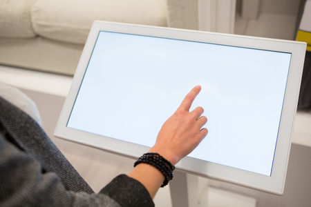 Photo pour A woman touching the screen of self service device in the store. - image libre de droit