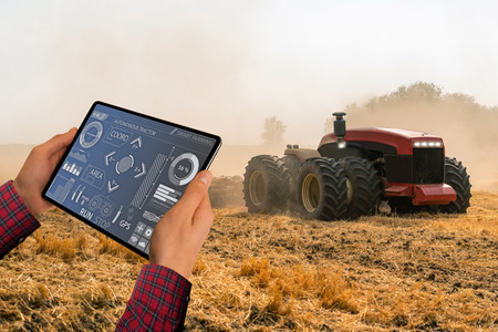 Photo for A farmer with digital tablet controls an autonomous tractor on a smart farm - Royalty Free Image