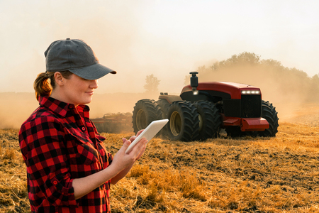 Foto de Woman  farmer with digital tablet controls an autonomous tractor on a smart farm - Imagen libre de derechos