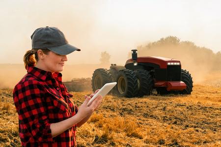 Photo pour Woman  farmer with digital tablet controls an autonomous tractor on a smart farm - image libre de droit
