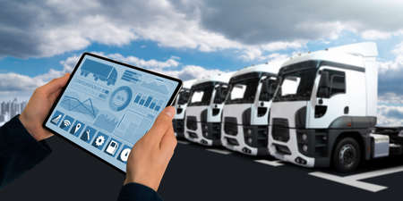 Photo pour Manager with a digital tablet on the background of trucks. Fleet management - image libre de droit