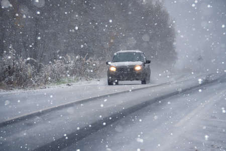 The car is driving on a winter road in a blizzard