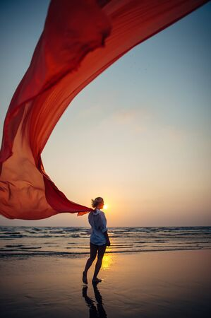 Photo pour Young woman walks along sandy beach of the sea, holding red long cloth in the wind against the background of setting sun. Freedom and vacation concept. Photo from the back, no face. - image libre de droit