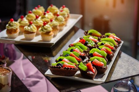 Photo pour Cakes with fresh fruit and berries on the holiday table, close-up. Cupcakes with cream. Sweet table at gala dinner. - image libre de droit
