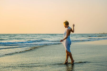 Photo pour Charming slender blonde in stylish dress stands in waves on the sea. Young woman walks barefoot along the surf and enjoys the rest. Female beauty and naturalness. - image libre de droit